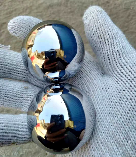 Hand with glove holding two chrome baoding balls