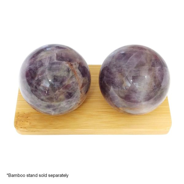 Amethyst baoding balls on a bamboo display stand