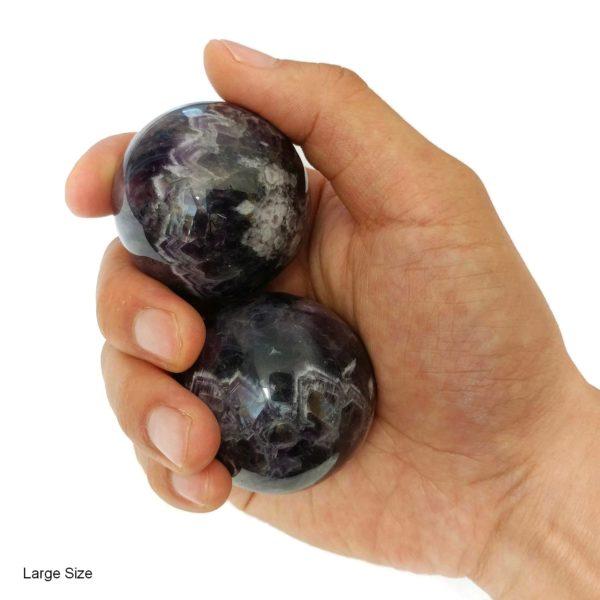 Hand holding large amethyst baoding balls
