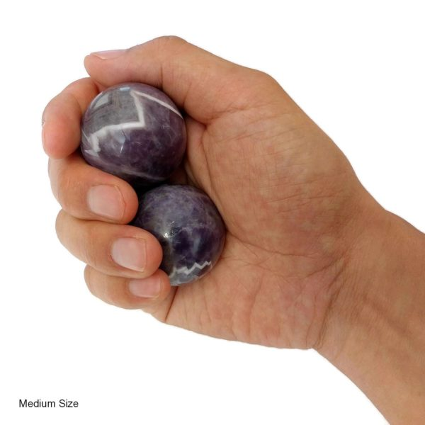 Hand holding medium amethyst baoding balls