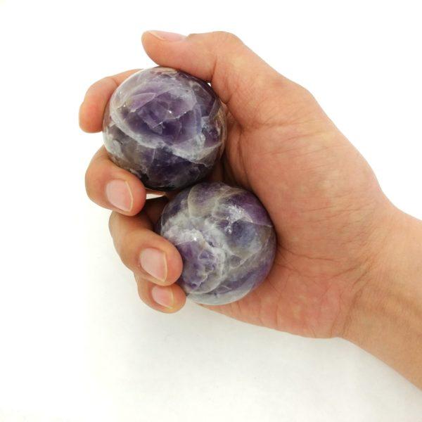 Hand holding large sized amethyst baoding balls