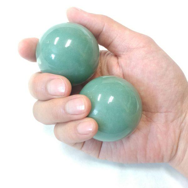 Hand holding large aventurine baoding balls