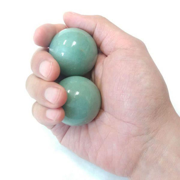 Hand holding medium aventurine baoding balls