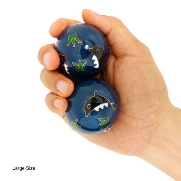 Hand holding large dolphin baoding balls