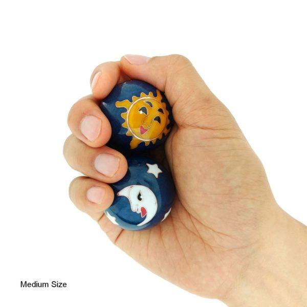 Hand holding medium sun and moon baoding balls
