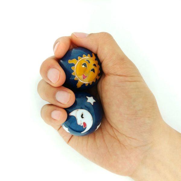 Hand holding medium sun and moon baoding balls.