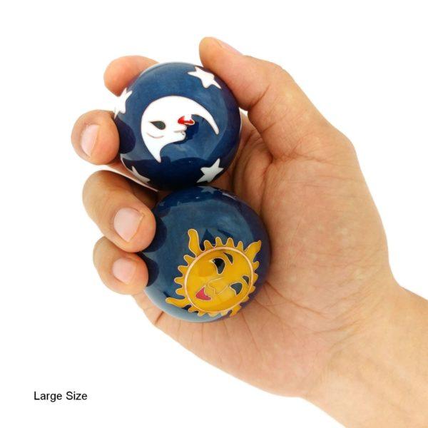 Hand holding large sun and moon baoding balls