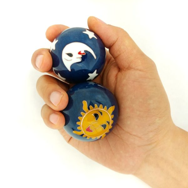 Hand holding large sun and moon baoding balls.