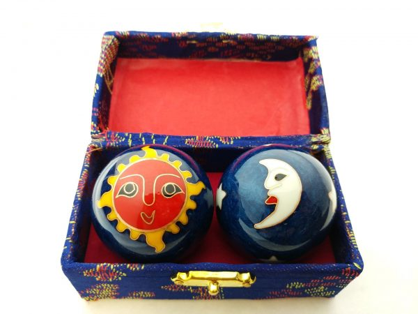 Blue baoding balls with sun and moon designs in a box
