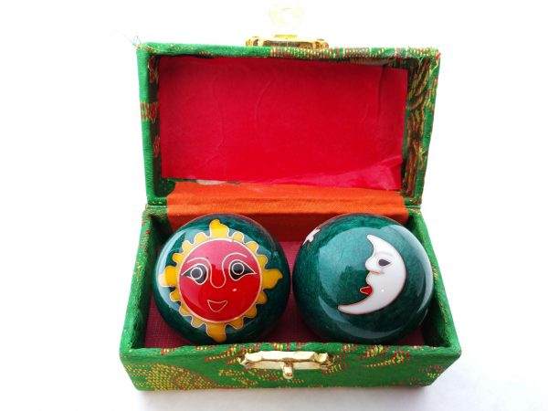 Green baoding balls with sun and moon designs in a box