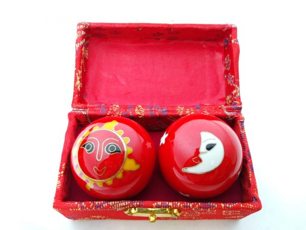 Red baoding balls with sun and moon designs in a box