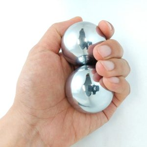 Hand holding two large chrome baoding balls