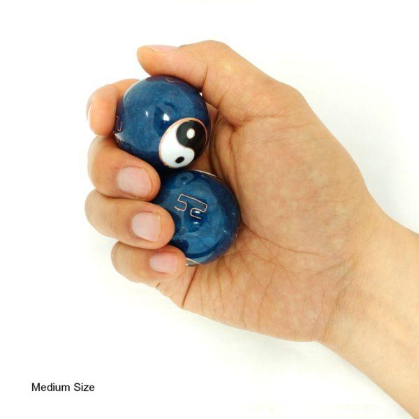 Hand holding medium yin yang baoding balls
