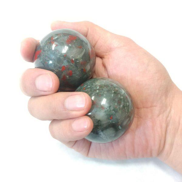 Hand holding large bloodstone baoding balls