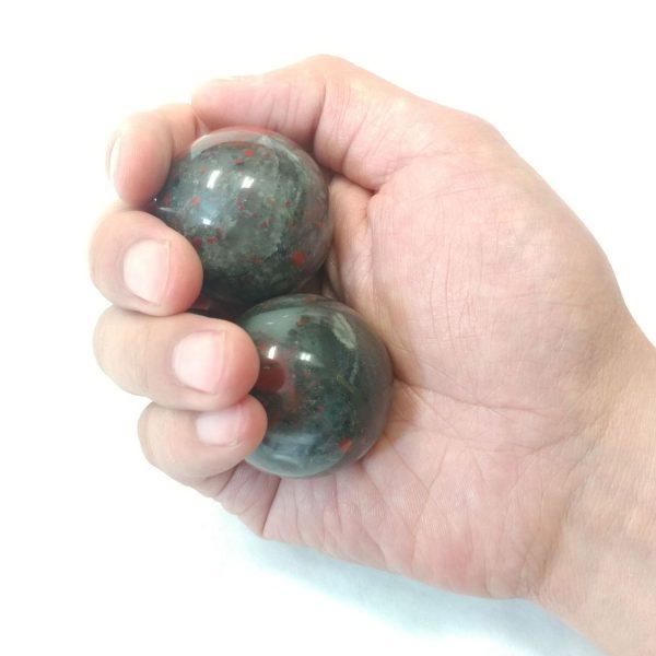 Hand holding medium bloodstone baoding balls