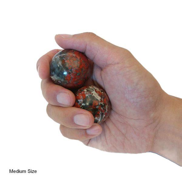 Hand holding brecciated jasper baoding balls