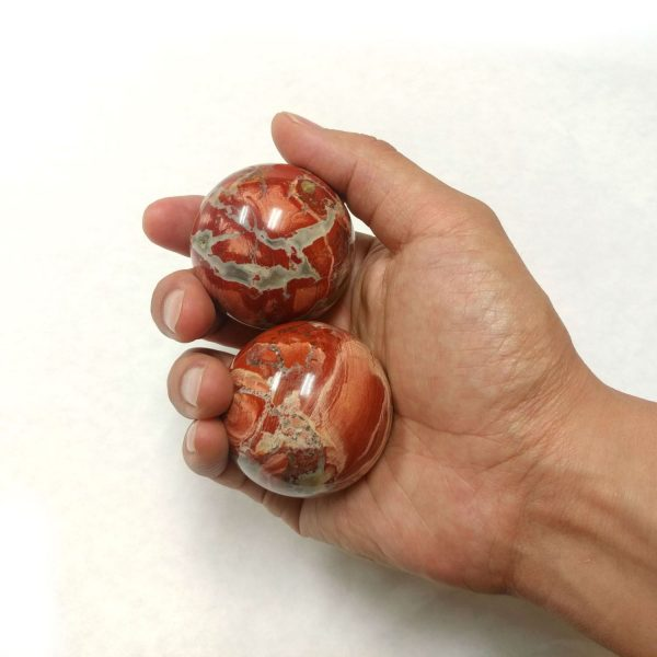 Hand holding large brecciated jasper baoding balls