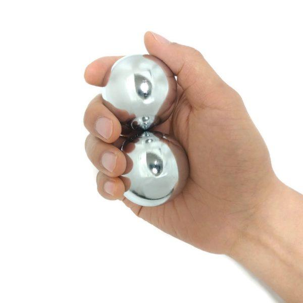 Hand holding large chrome baoding balls