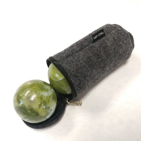 Baoding balls made from green jade gemstone in a carry bag