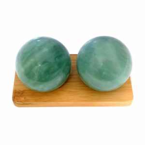 Green jade baoding balls on bamboo display stand