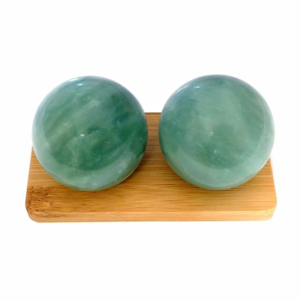 Green jade baoding balls on bamboo display stand
