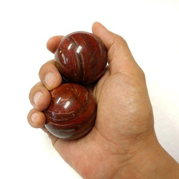 Hand holding large snakeskin jasper baoding balls