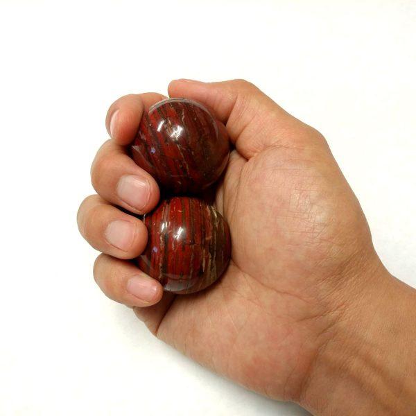 Hand holding medium snakeskin jasper baoding balls