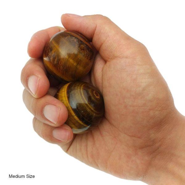 Hand holding tigers eye baoding balls