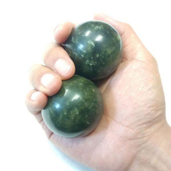 Hand holding large xiuyan jade baoding balls