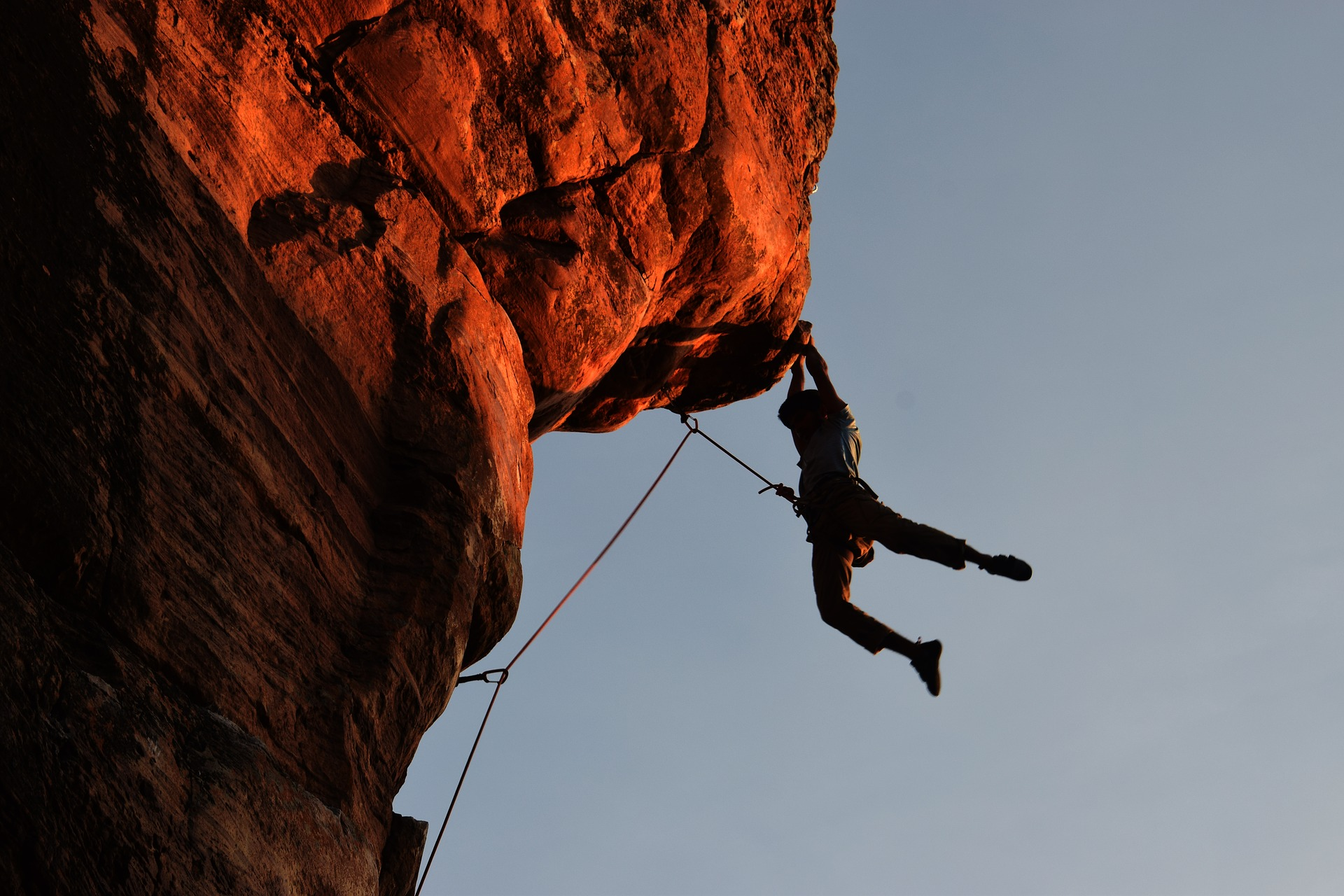 Man hanging on to cliff with his hands