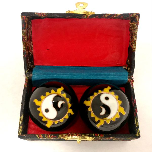 Black baoding balls with sun and moon yin yang design in a box