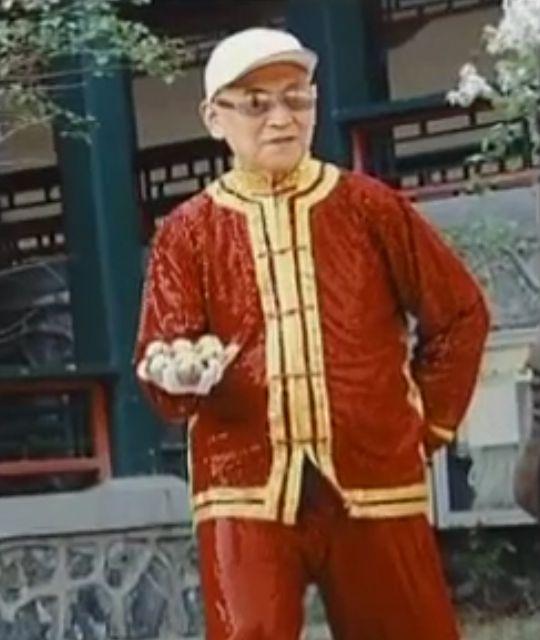 Li Zhanchun in formal Chinese clothing using baoding balls