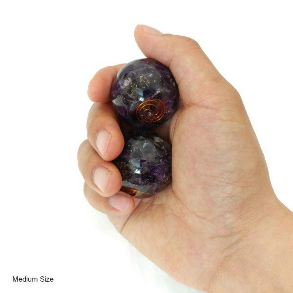 Hand holding amethyst orgonite baoding balls