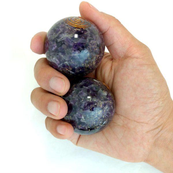 Hand holding 2 large amethyst orgonite baoding balls