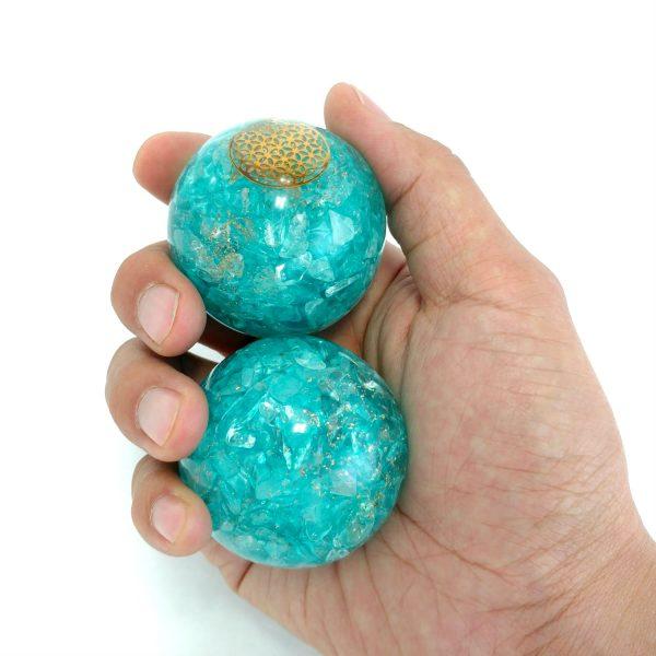 Hand holding large aquamarine orgonite baoding balls