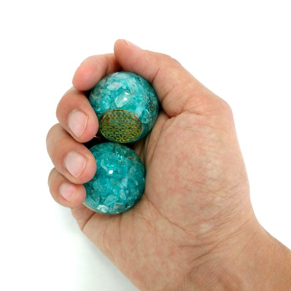 Hand holding medium aquamarine orgonite baoding balls