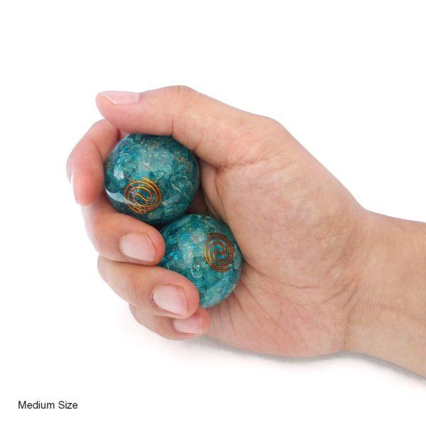 Hand holding aquamarine orgonite baoding balls