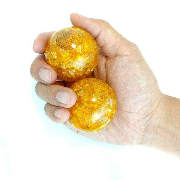 Hand holding 2 large citrine orgonite baoding balls