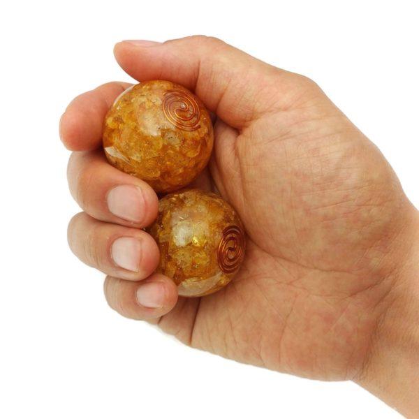 Hand holding medium citrine orgonite baoding balls