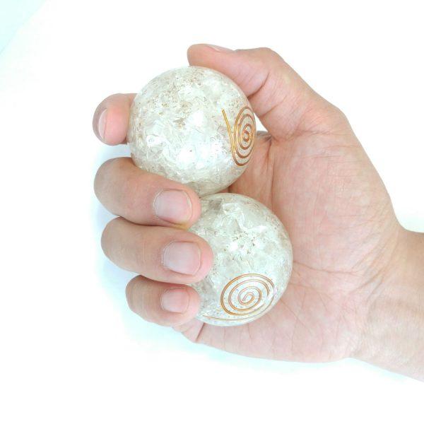Hand holding 2 large quartz orgonite baoding balls