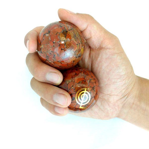 Hand holding 2 large red jasper orgonite baoding balls