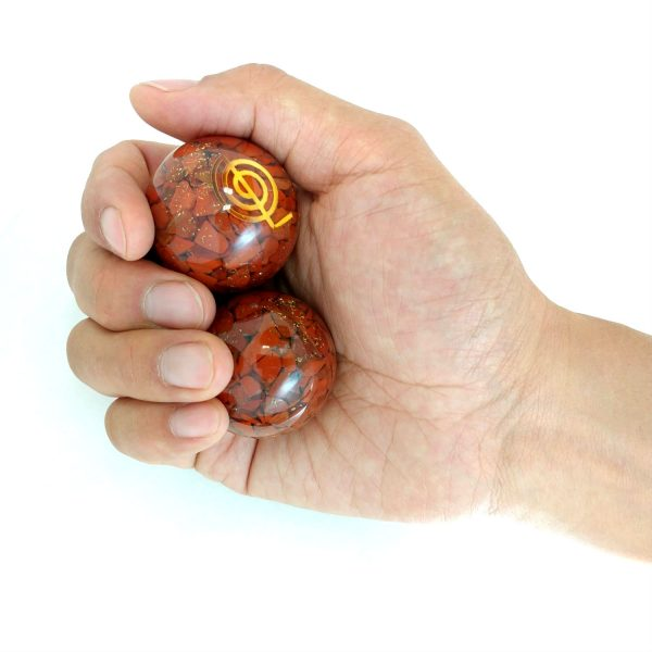 Hand holding 2 medium red jasper orgonite baoding balls