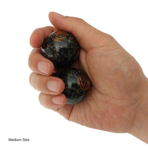 Hand holding medium tourmaline baoding balls