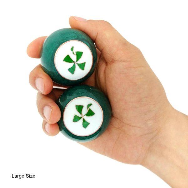 Hand holding large four leaf clover baoding balls