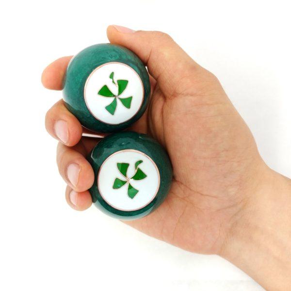 Hand holding large size 4 leaf clover baoding balls