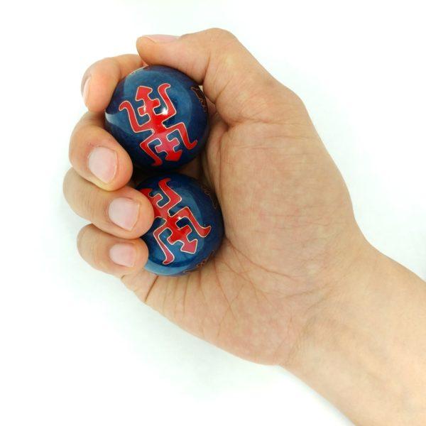 Hand holding medium size longevity baoding balls
