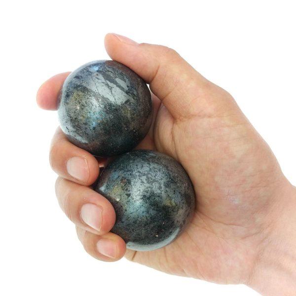 Hand holding large hematite baoding balls