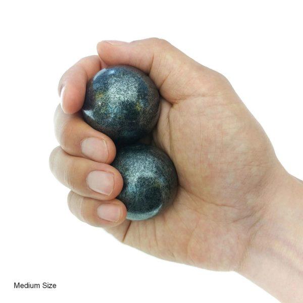 Hand holding medium hematite baoding balls