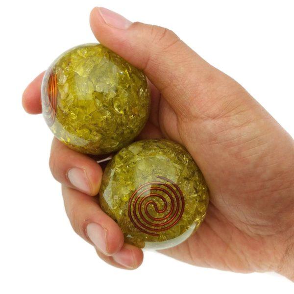 Hand holding peridot orgonite baoding balls