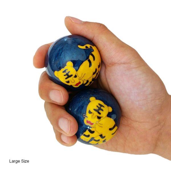 Hand holding large tiger baoding balls